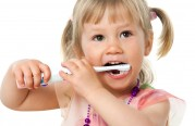 Close up portrait of little girl brushing teeth